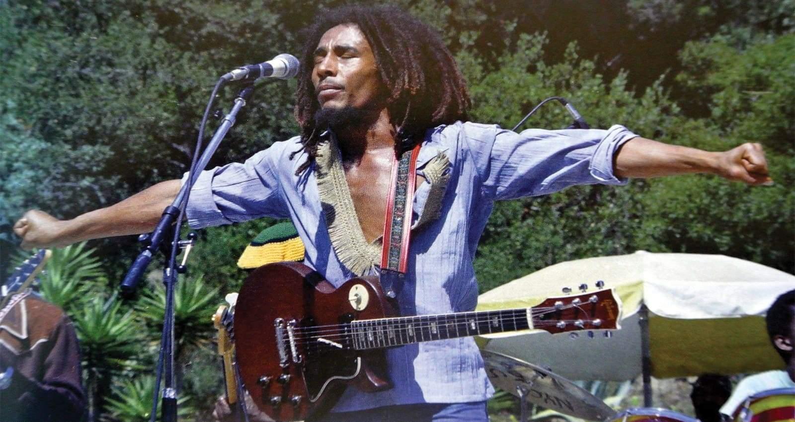 Bob Marley roi du reggae, sur scène les bras ouvert comme le christ
