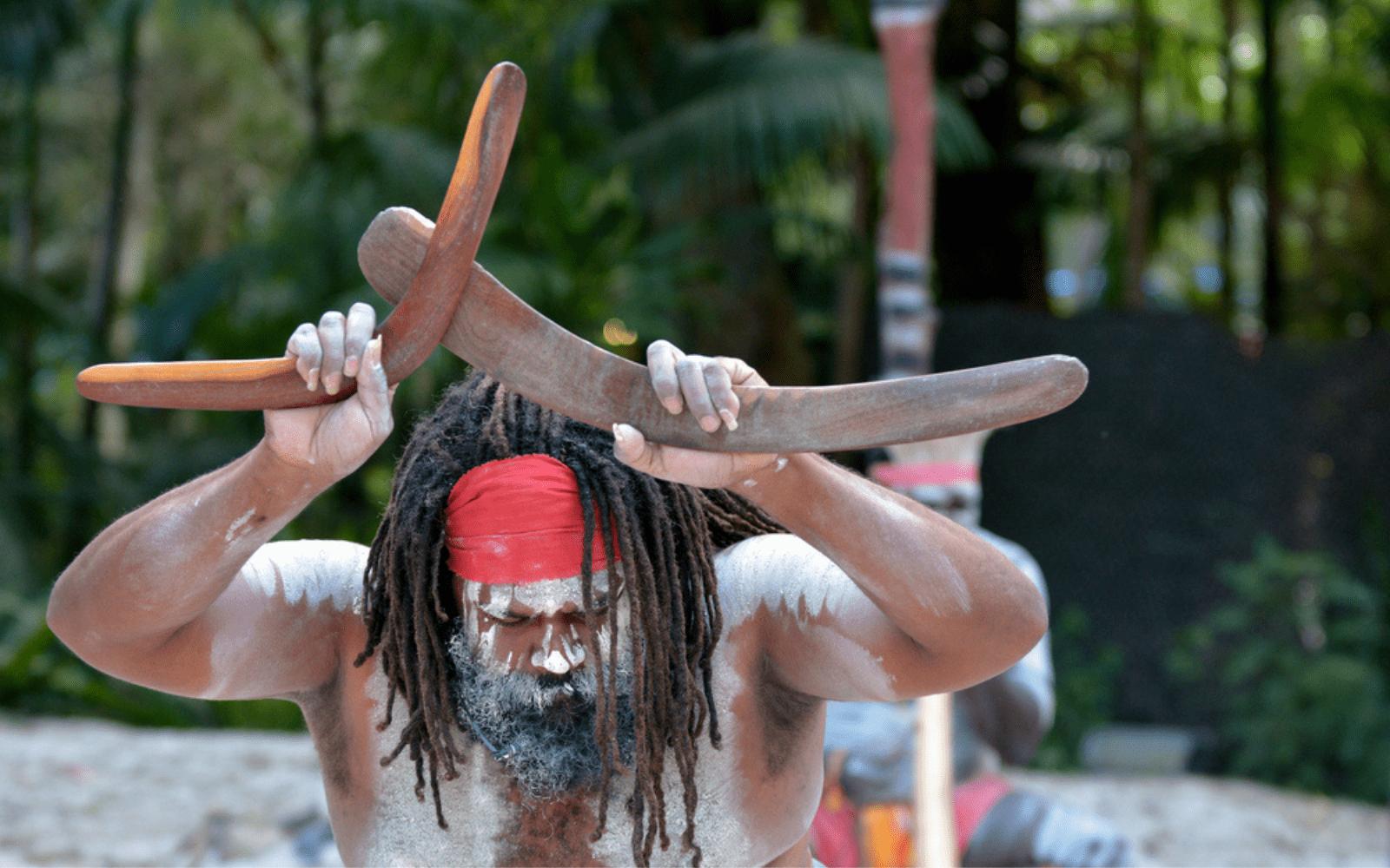 aborigène d'Australie avec dreadlocks et des boomerangs dans les main, en tenu traditionnelle pendant une ceremonie