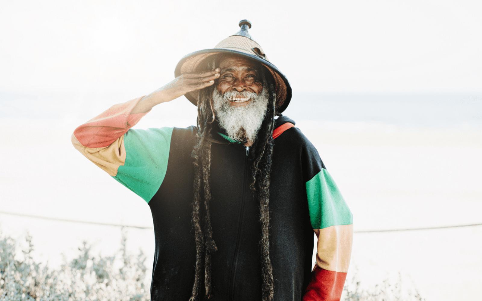 Photo d'un vieux rastafari portant de longue dreadlocks et des habits vert jaune rouge