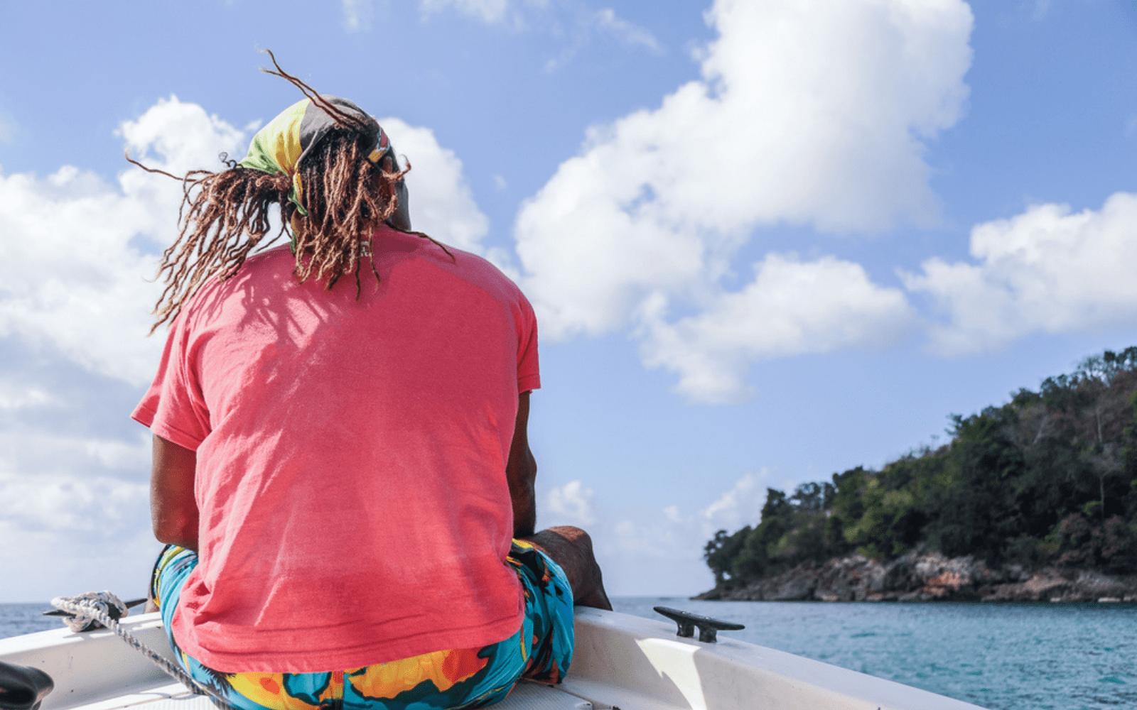 Jeune rasta de dos dreadlocks dans le vent, assis à la pointe d'une bateau
