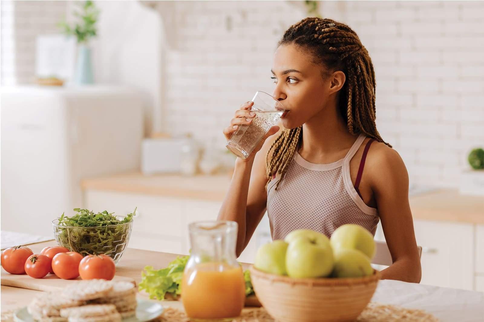 Femme noire avec dreadlocks, sportive, prenant son petit dejeuner. Fruits et legumes.