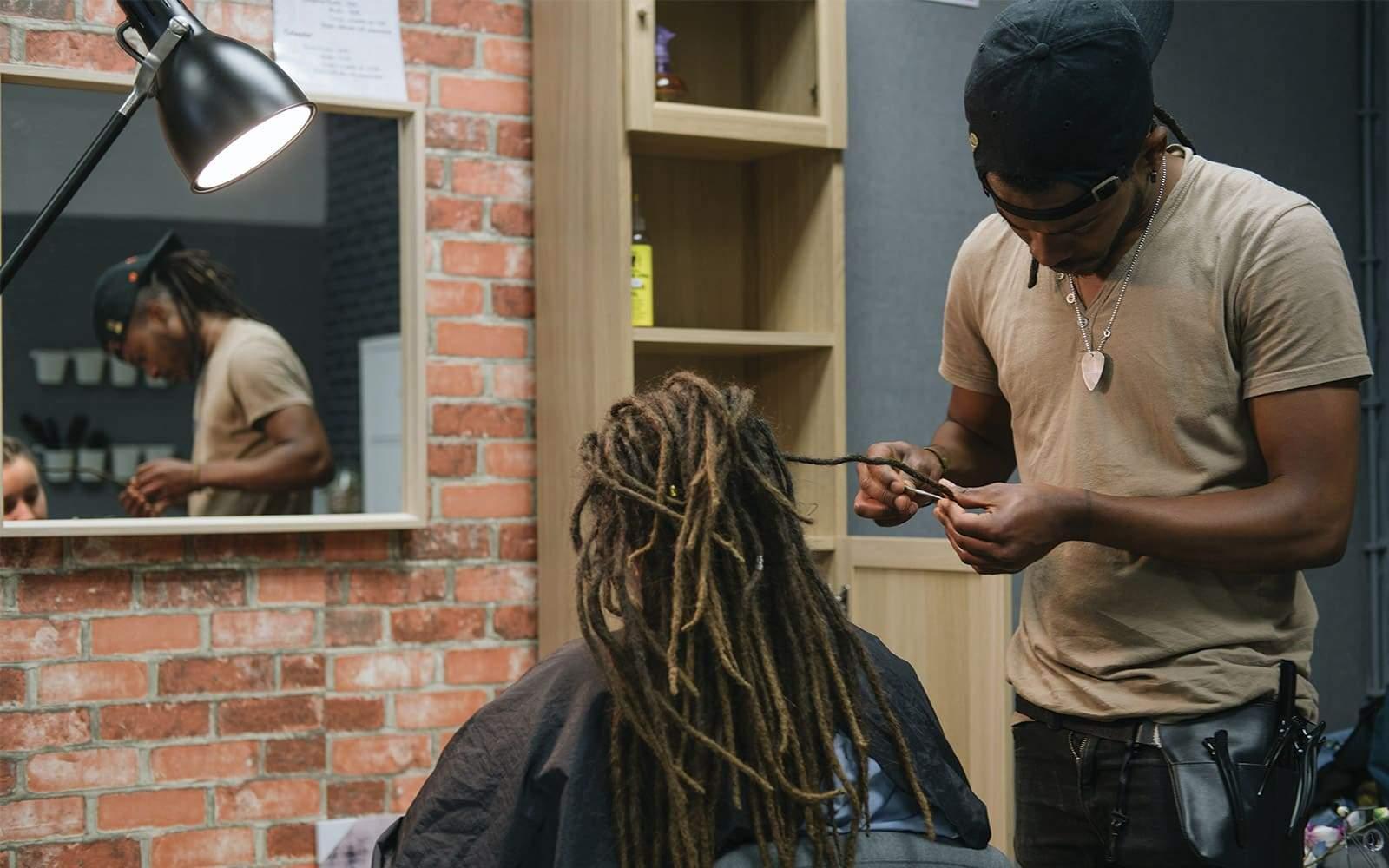 Homme faisant des dreadlocks pour jeune femme dans salon coiffure