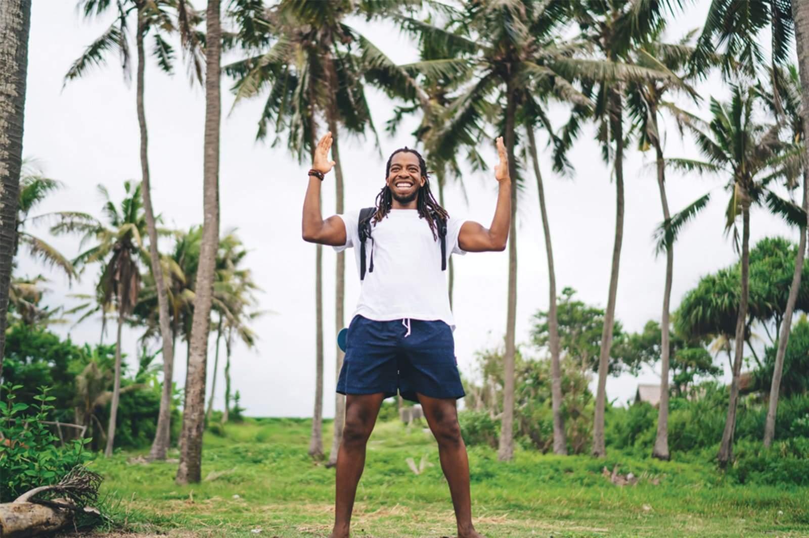 Homme noir avec Dreadlocks se tenant debout entre des palmiers, super heureux et en forme