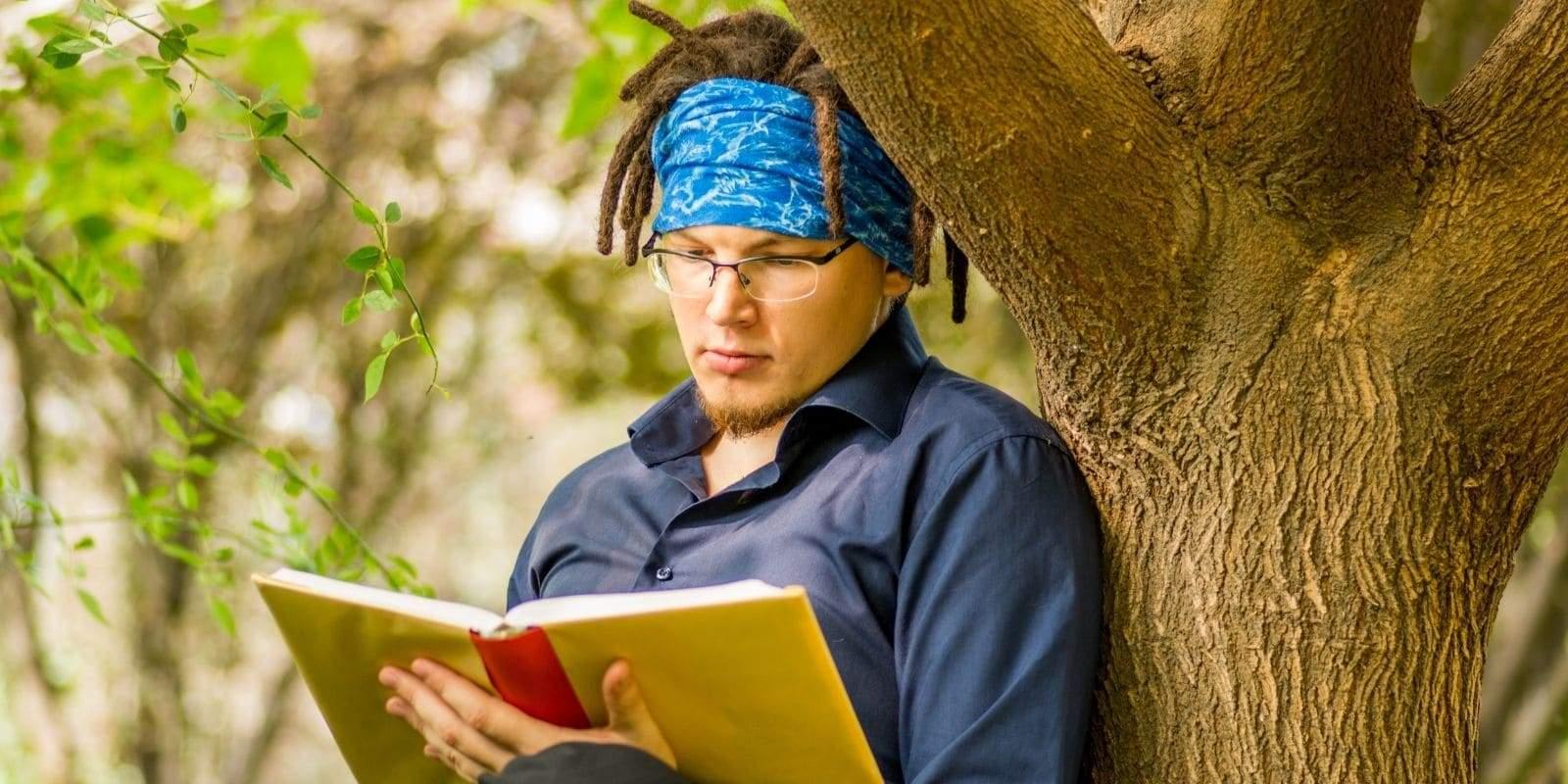 Homme avec dreadlocks pose contre un arbre en train de lire