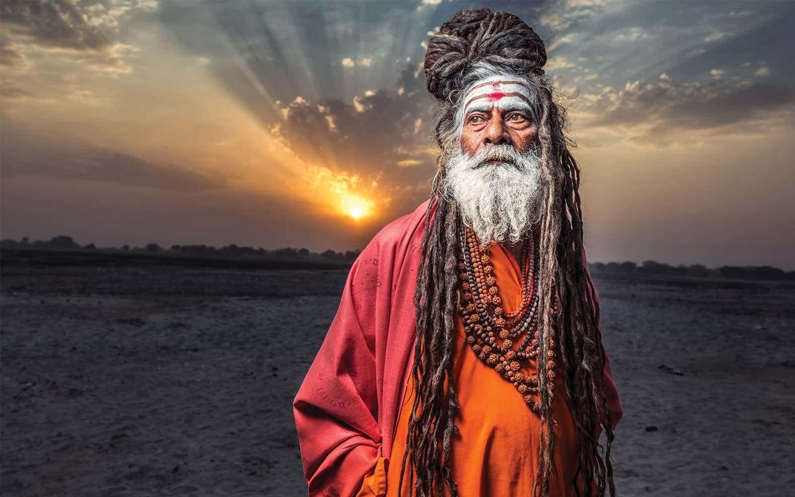 Sadhu portant des dreadlocks avec couché de soleil derriere lui
