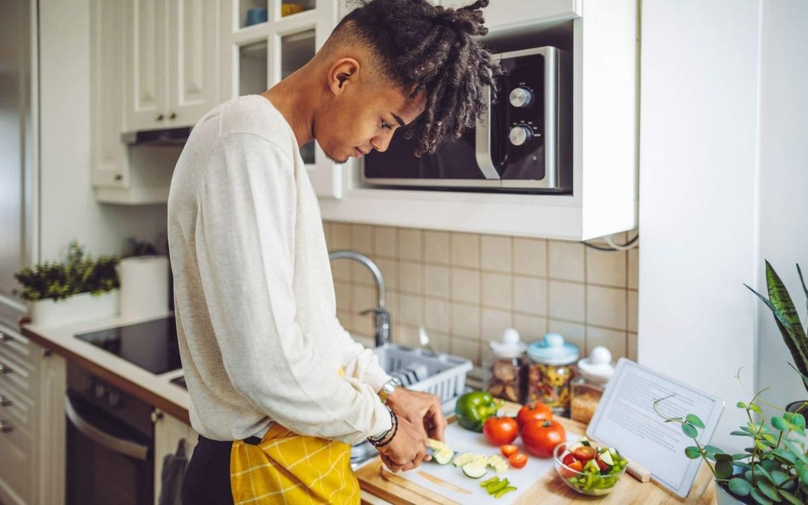 Jeune rasta cuisinant des légumes