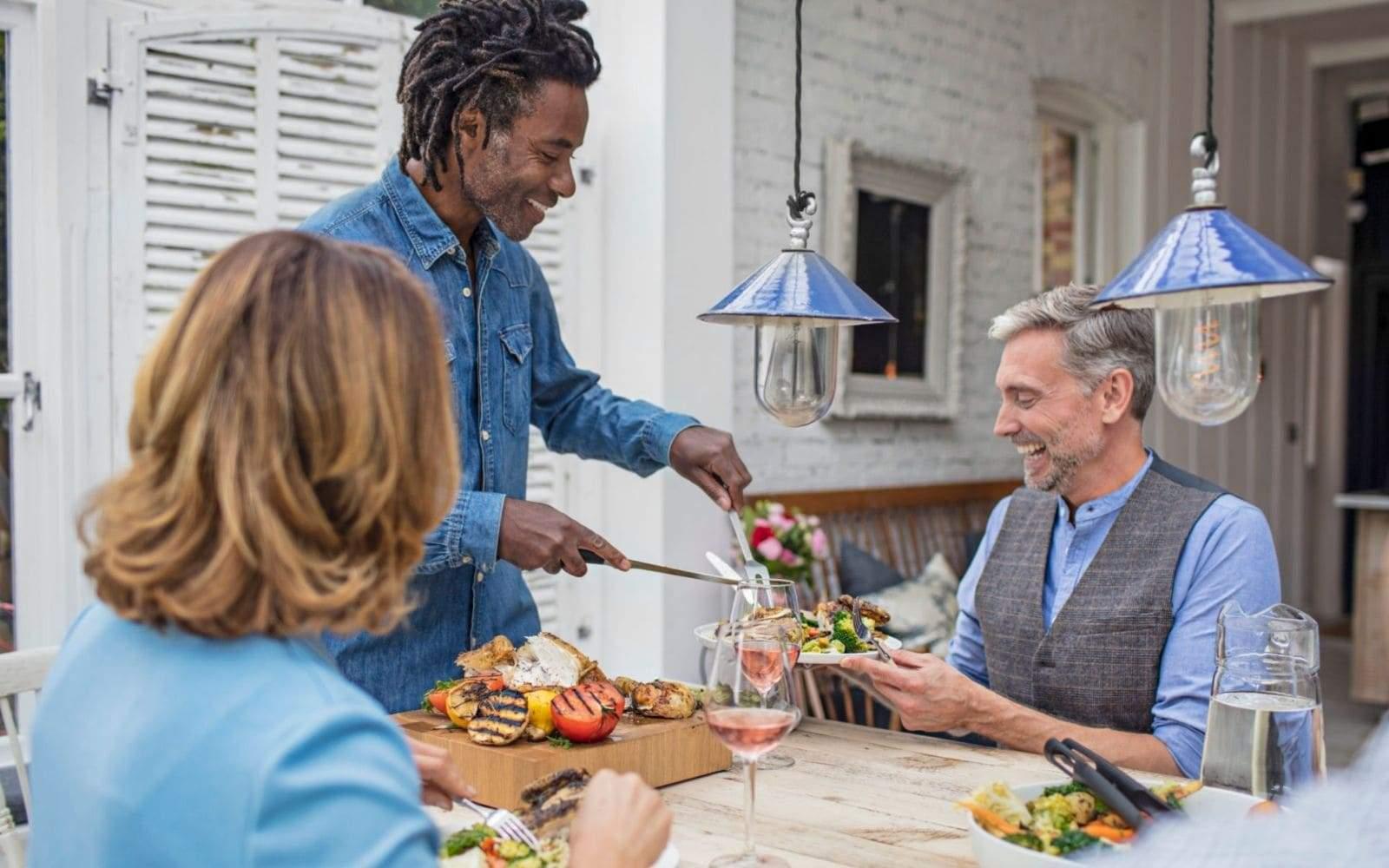 Homme avec dreadlocks servant a manger a des amis