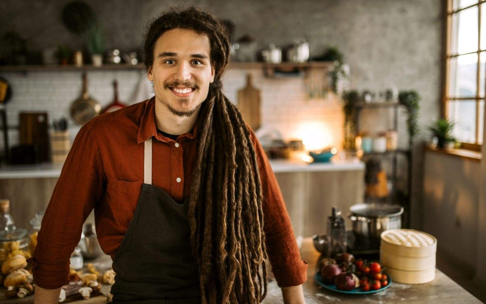 Cuisinier avec dreadlocks souriant assis sur sa table