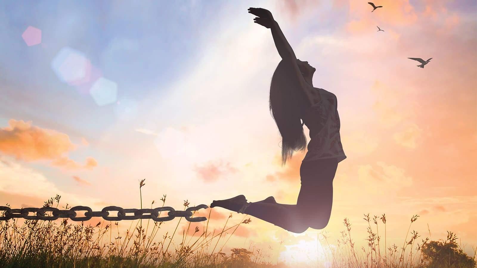 Une femme saute de joie avec les chaîne de l'esclavage détruites.